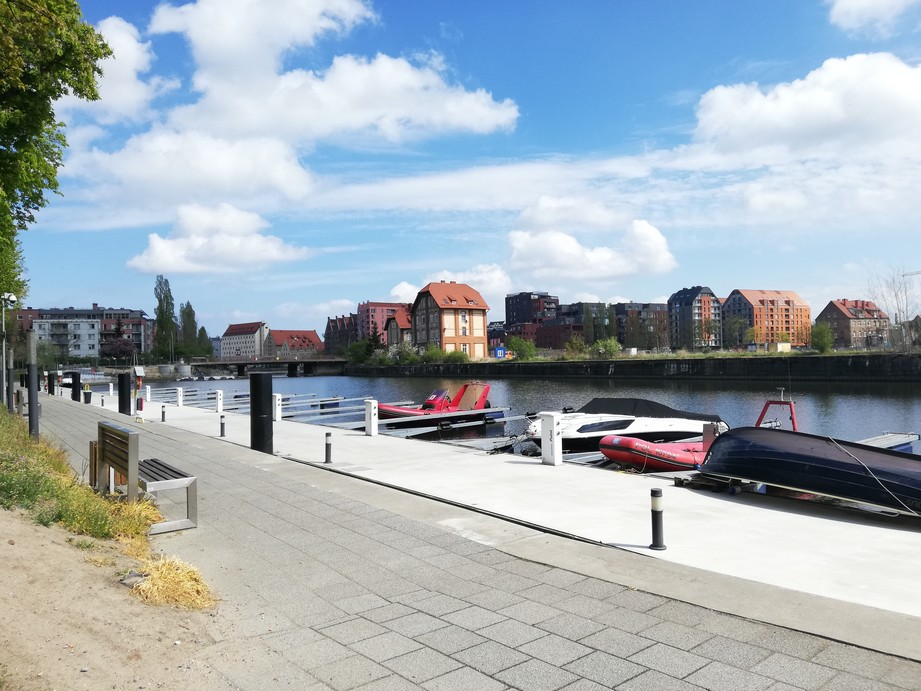 Gdańsk. The Żabi Kruk Harbour. Contemporary photographs. The harbour and the Old Motława canal. The photograph presents buildings located near the Old Motława canal, where some dinghies and motorboats are moored.