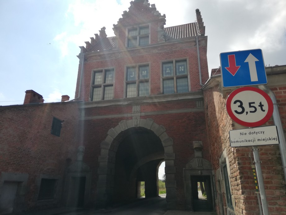 The Lowland Gate seen from Dolna Brama St. Contemporary photographs. The photograph features a brick building decorated with some elements made of light grey stone. The object houses an arched tunnel. On both sides of the tunnel there are pedestrian passages. Over the tunnel (at the level of the second floor) there are three windows and one window in the attic. All the windows are rectangular and they are set in stone frames. There are two symmetrical brick walls adjoining the building.