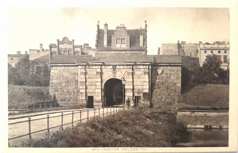 Gdańsk. The Lowland Gate – a postcard. Archive photographs. A black-and-white photograph presents the southern façade of the building (seen from the moat) which is built from light grey stone blocks. In the central part of the object there is an arched tunnel with two rectangular pedestrian passages on its both sides. Over the tunnel there is Gdańsk coat of arms. There is a road cobbled with flagstones leading to the gate. There is some water nearby. In the background some historic buildings can be observed.