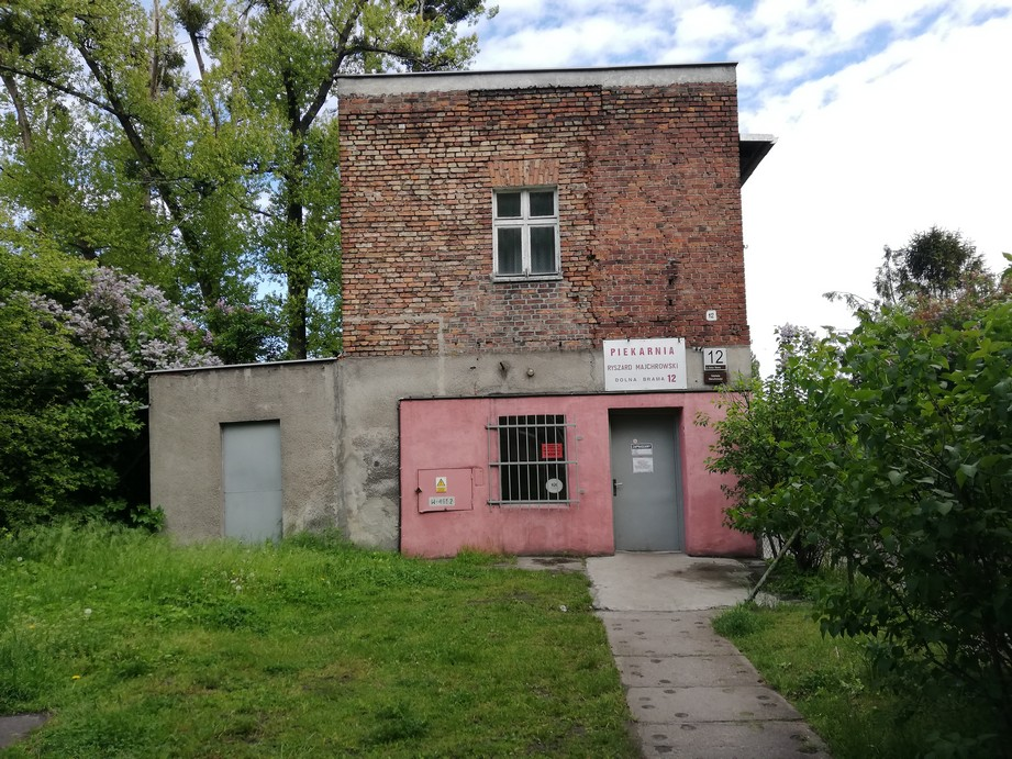 """Gdańsk. The Majchrowski Bakery. Contemporary photographs. The building which has been housing the Majchrowski Bakery since 1970s. The photograph presents a small brick building with the ground floor covered with plaster and partially covered with dark pink paint. The ground floor has a grey door in the centre and a window with bright metal bars. Above the entrance door there is a white board with a red inscription: """"Bakery. Ryszard Majchrowski. 12 Dolna Brama St."""" At the level of the first floor there is no plaster on the wall and the bricks are visible. There is one window covered with a curtain. The building is of a cubical shape and there is a small extension adjoining its left side. In front of the building there is a lawn and a small deciduous tree. There are some more trees in the background."""