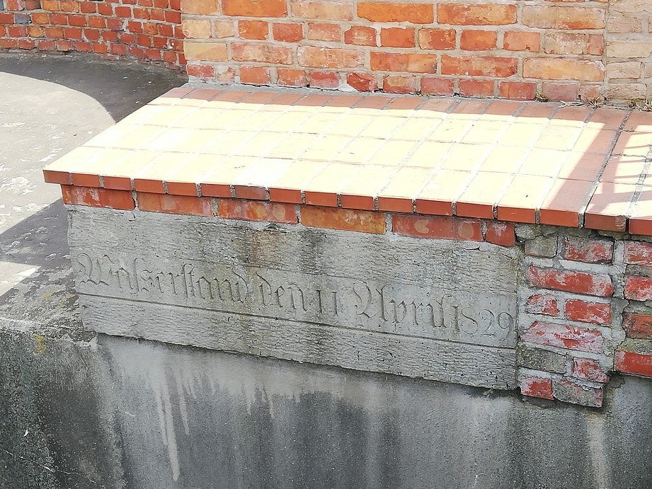 Gdańsk. The auxiliary mill. Contemporary photographs. A stone slate with the water level marks from the great flood of 1829. The  photograph presents the brick wall with the information engraved in stone, indicating the water level during the great flood of 1829.