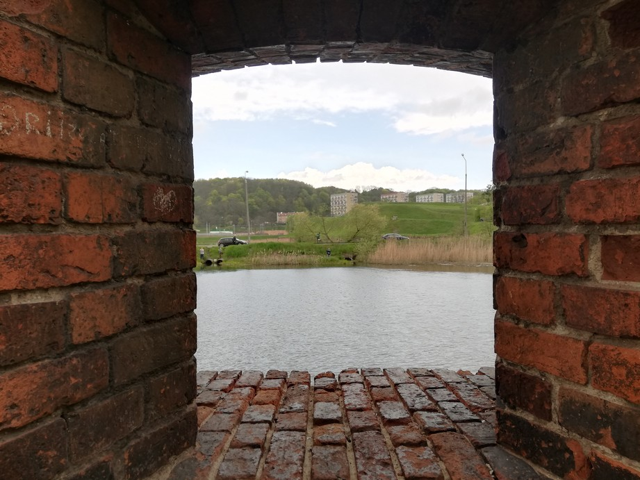 Gdańsk. St Gertrude Bastion. Contemporary photographs. The photograph presents a view from a window of an old brick building to St Gertrude Bastion. There is also the river, a grassy hill, some apartment blocks and a wood in the background.