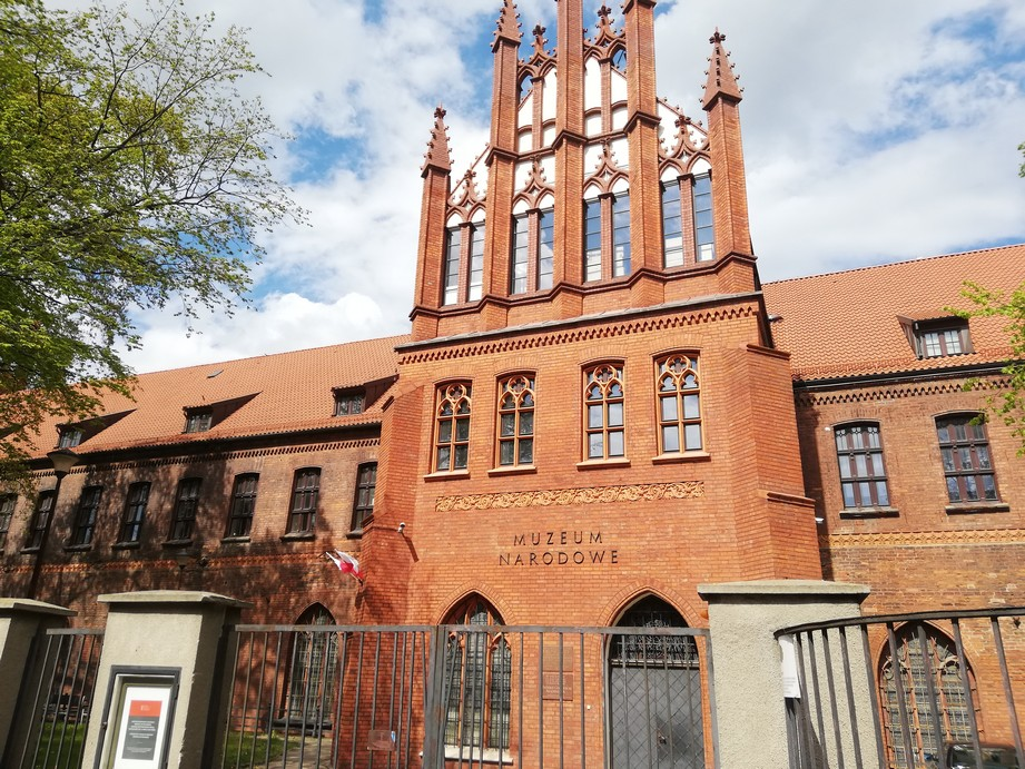"""Gdańsk. The National Museum. Contemporary photographs. The photograph presents a big, historic brick building which used to be a Franciscan monastery. The building is an example of the late Gothic architecture. In front of the building there is a metal gate and a fence. Above the entrance door there is an inscription """"The National Museum""""."""