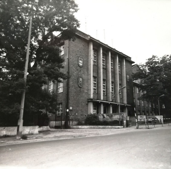 Gdańsk. The Polish Gymnasium. Archive photographs. A post-war photograph of the former Polish Gymnasium. The black-and-white picture presents the entrance to the building and its right wing. The building is made of bricks. On the left side of the entrance, at the levels of the first and the second floors, there are two emblems attached to the wall: one presents Gdańsk coat of arms and the other - the school badge. There are trees on the right and on the left of the picture.