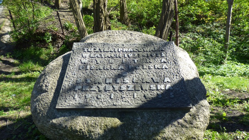 """Gdańsk. The Polish Gymnasium. Contemporary photographs. The stone commemorating Stanisława Przybyszewska. The photograph presents a big grey stone on the grass. There are some trees in the background. There is a large metal plaque attached to the stone with an embossed inscription: """"Stanisława Przybyszewska, an outstanding Polish writer (1901-1935), lived and worked here during the years 1923-1935."""""""