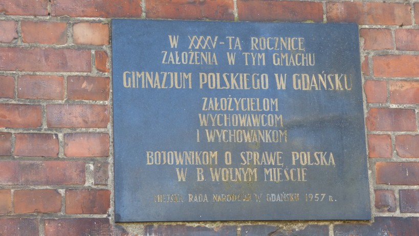 """Gdańsk. The Polish Gymnasium. Contemporary photographs. A plaque commemorating the founders, teachers and students of the Polish Gymnasium. The photograph presents a black stone plaque with a golden inscription. It is attached on the right side of the entrance to the building of the Polish Gymnasium. The inscriptions says: """"To commemorate the 35th anniversary of the founding of the Polish Gymnasium in Gdańsk – to honour its founders, teachers and students who fought for the Polish cause in the former Free City. The Municipal National Council 1957."""""""
