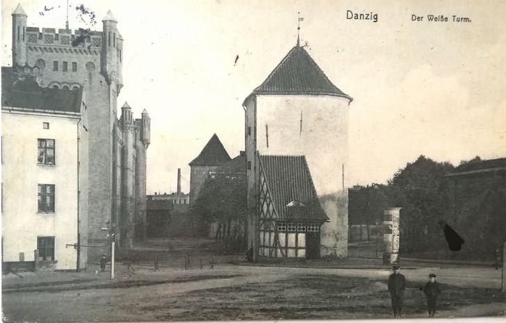 Gdańsk. The White Tower. Archive photographs. A black-and-white postcard. The photograph presents a historic medieval tower located in the town centre at the Old Suburb. The building is of a round shape and is covered with a conical roof. The rear part of the tower is not rounded – the wall surface is flat there. Next to the tower there is a small outhouse with a steep roof. There are also some brick buildings visible nearby the tower, however they did not survive until the present moment. In front of the tower there are two people.