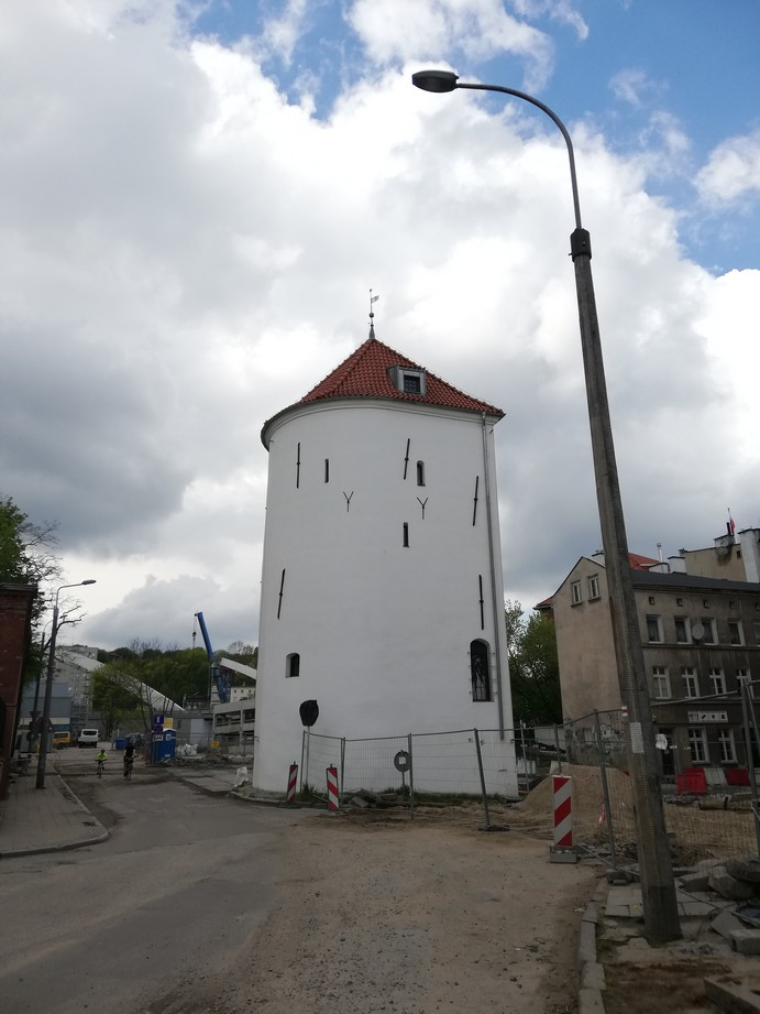 Gdańsk. The White Tower. Contemporary photographs. The White Tower after the renovation. The photograph presents a historic medieval tower located in the town centre at the Old Suburb. The white building is of a round shape and is covered with a conical roof. The rear part of the tower is not rounded – the wall surface is flat there. The tower walls feature a number of small arched loopholes. The roof is covered with brick tiles and there is one window. There is some renovation work going on in the vicinity of the White Tower.