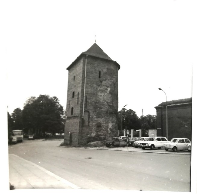 Gdańsk. The White Tower. Archive photographs. A post-war black-and-white postcard. The photograph presents a historic medieval tower located in the town centre at the Old Suburb. The building is of a round shape and is covered with a conical roof. The rear part of the tower is not rounded – the wall surface is flat there. The tower is not plastered so the battered bricks are visible. On the right side of the photograph there is a parking lot and on the left side there is an asphalt road.