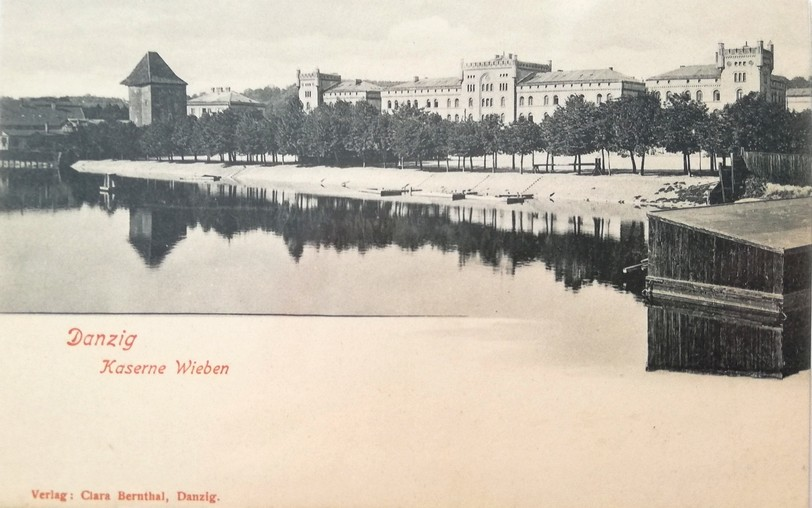 Gdańsk. The Wiebe Barracks. Archive photographs. A black-and-white postcard. In front of the building there is a river and a dense line of deciduous trees. Behind that line, the massive barracks building can be observed at the level of its first floor. In the postcard some turrets can be observed on both (left and right) extreme parts of the buildings. The turrets do not exist at present. In the background the old city buildings can be seen.