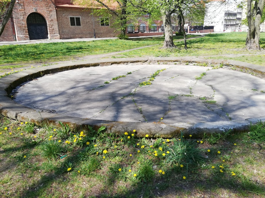 Gdańsk. Embankment Square. Contemporary photographs. The stone base of a fountain which used to be located at Embankment Square. The base is round and it is made of grey stone. The stone floor is broken. It is surrounded by grass and trees. There is a brick building in the background.