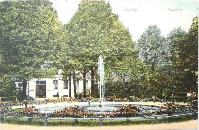 Gdańsk. Embankment Square. Archive photographs. A postcard features the fountain at Embankment Square. The fountain base is round and filled with water. From the middle of the fountain a single jet of water springs up to the sky. Near the fountain there are numbers of colourful flowers. The object is surrounded with a low, dark-coloured fence. There is a lot of greenery near the fountain. In the background there are deciduous trees and a white building. There are also some benches next to the fountain.