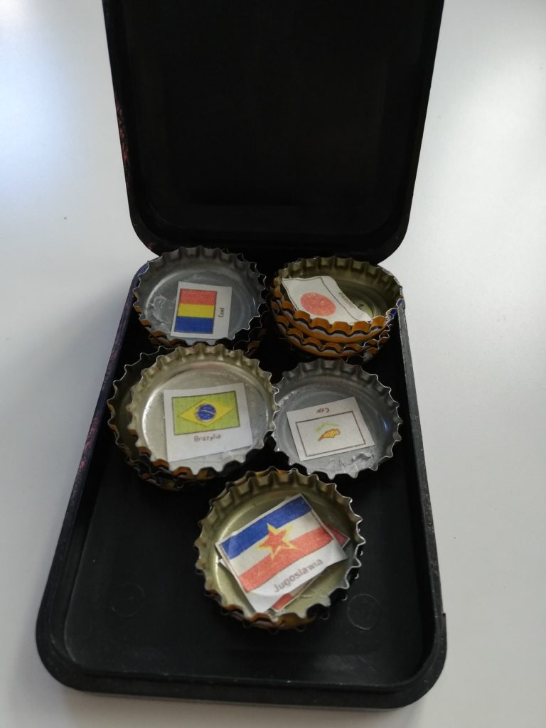 The photograph presents a black box with some bottle caps in it. Inside each bottle cap some small pieces of paper are stuck. These are colourful national flags and the names of the countries: Japan, Brazil, Cyprus, Yugoslavia.