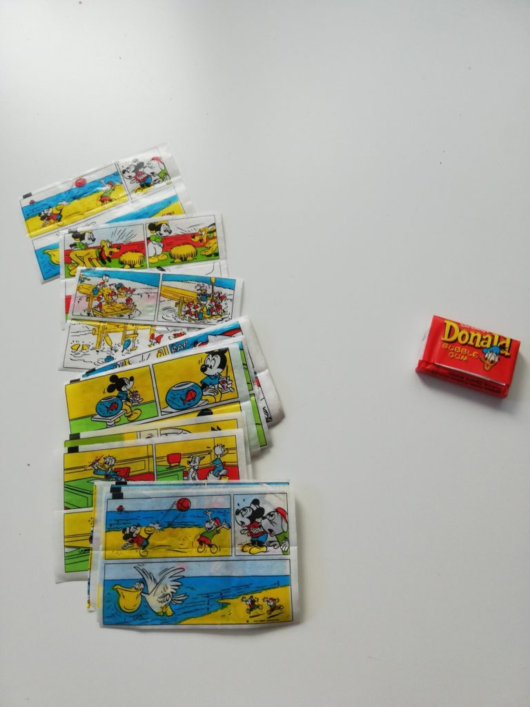 """The photograph presents a collection of various chewing gum stickers with Donald Duck. The stickers present adventures of such characters as Mickey Mouse, Donald Duck, Pluto. The photograph also features an old, originally packed piece of chewing gum. The wrapping paper is red with a yellow inscription """"Donald Bubble Gum"""" and Donald Duck's head."""