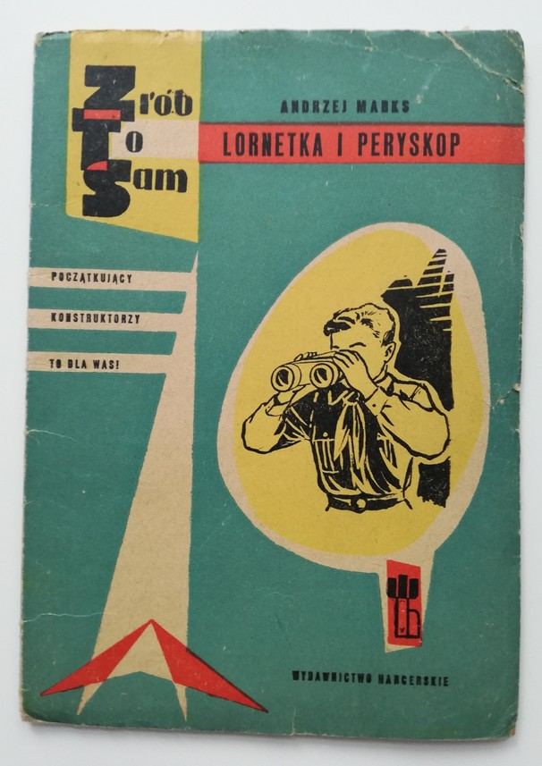The photograph features an old, slightly tattered DIY instruction book Do-it-yourself. Binoculars and Periscope by Andrzej Marks. The book has a blue cover with a black-and-white illustration presenting a boy looking through his binoculars. On the left side there is an inscription Beginner Constructors – It Is For You! Scout Publishing House.