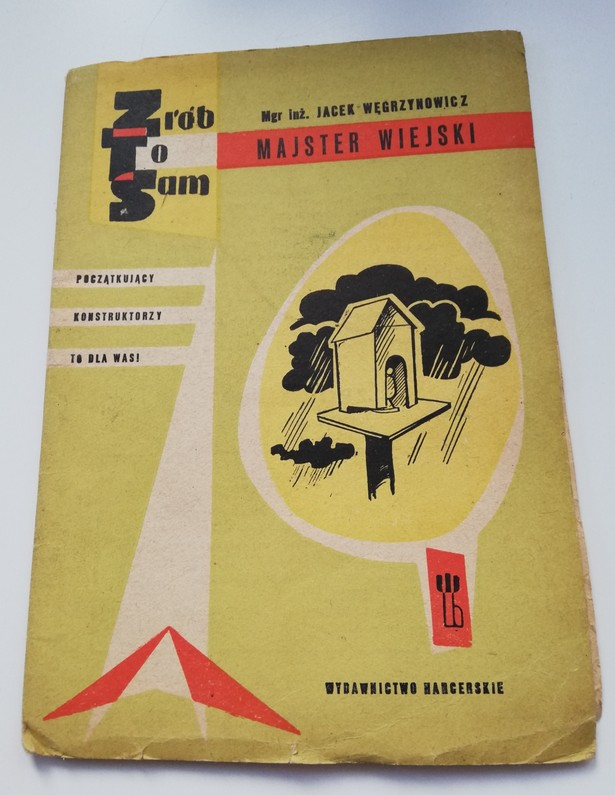 The photograph features an old, slightly tattered DIY instruction book Do-it-yourself. A Rural Handyman by Jacek Węgrzynowicz. The book has a yellow cover with a black-and-white illustration presenting a bird feeding house on a stick. On the left side there is an inscription Beginner Constructors – It Is For You! Scout Publishing House.