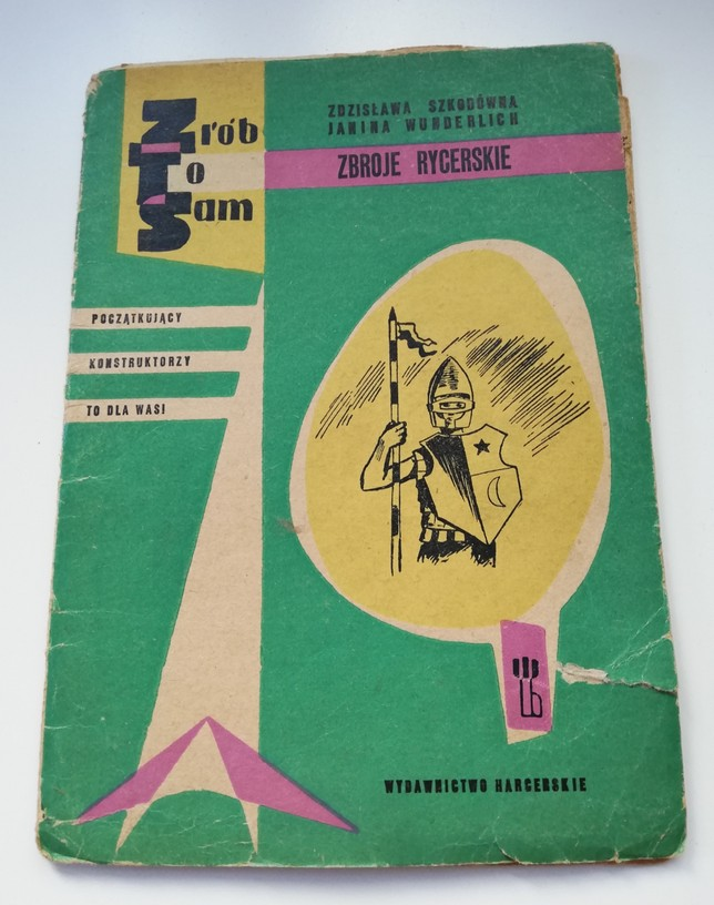 The photograph features an old, slightly tattered DIY instruction book Do-it-yourself. Knight Armours by Zdzisława Szkodówna and Janina Wunderlich. The book has a green cover with a black-and-white illustration presenting a knight with a shield and a lance. On the left side there is an inscription Beginner Constructors – It Is For You! Scout Publishing House.