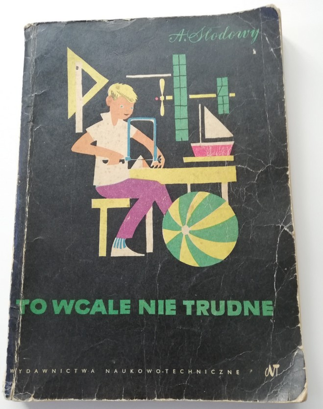 The photograph presents a cover of a book by Adam Słodowy: It Is Not Difficult At All. The cover is black, the title is green and in the centre there is a colourful illustration of a boy sitting at his workshop with a saw and a piece of wood.