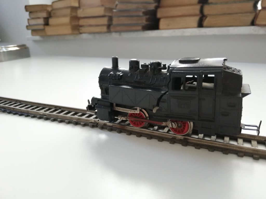 The photograph presents a toy engine on the tracks. The engine is black with red wheels. The tracks are brown. There are some books visible in the background.