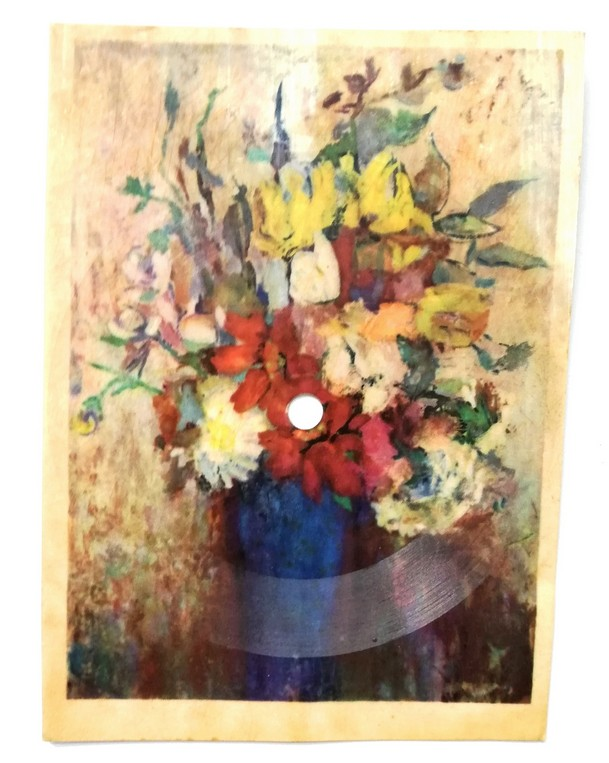 The photograph presents a sound postcard (a type of a vinyl record) with a picture of colourful flowers in a blue vase printed on it.