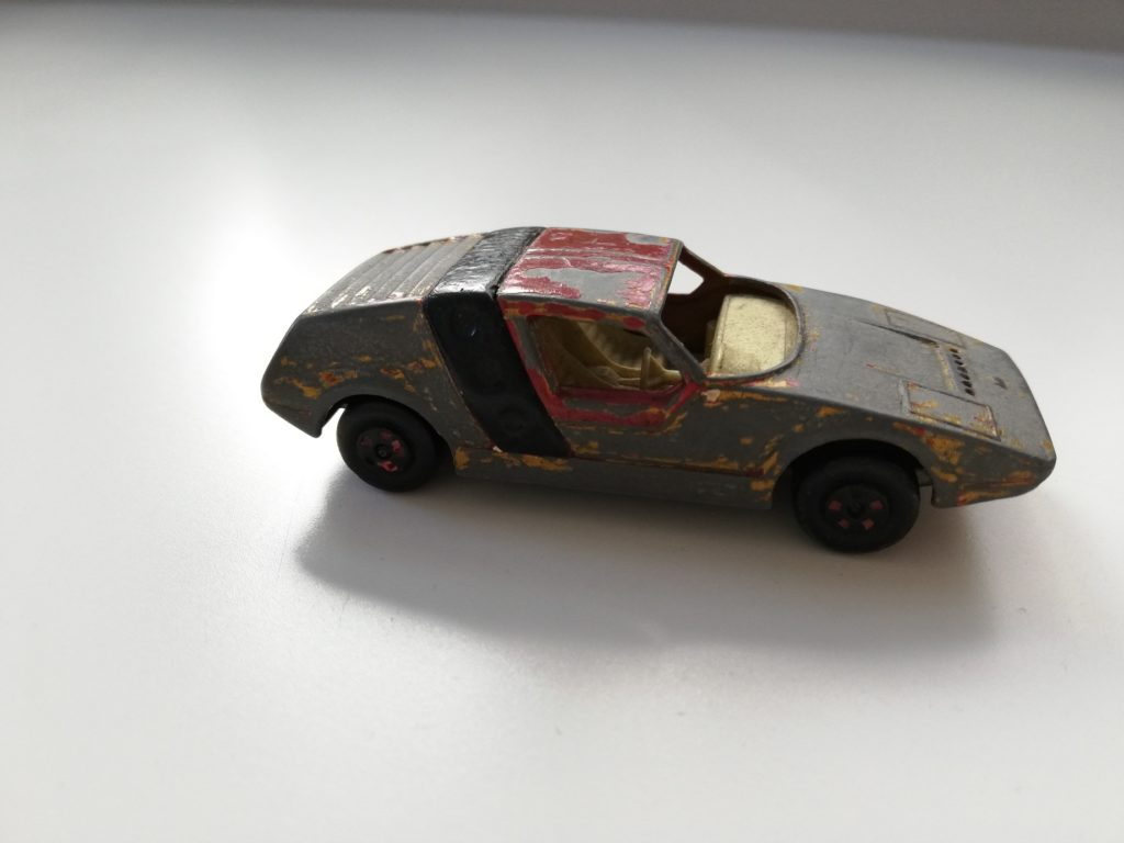 The photograph presents a heavily battered toy car. Some remains of red, black and white paint can be still seen on its body. The car does not have any glass windows. The inside of the car is of a sandy colour – there are two seats and a steering wheel. The tyres are black.