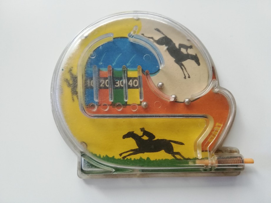 The photograph presents a plastic toy which is a labyrinth for some metal balls. At the bottom there is a little stick with a spring allowing the player to push the balls up into the labyrinth. Under the transparent upper part of the labyrinth there is a colourful picture featuring horse riders. At the top of the labyrinth there are four pockets for the balls with the number of points printed on them: 10, 20, 30, 40.