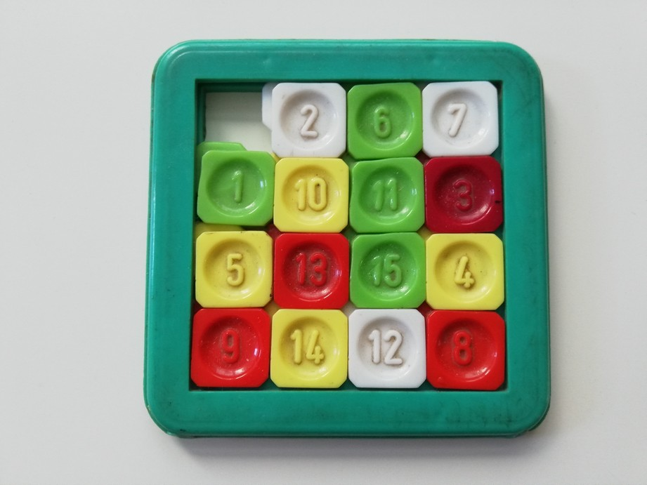 The photograph presents a colourful plastic toy which is composed of a green frame and little square elements inside. Each square element has a number on it. The square elements are connected with each other but it is possible to move and shuffle them. One spot is empty in order to allow the player to move other square elements.
