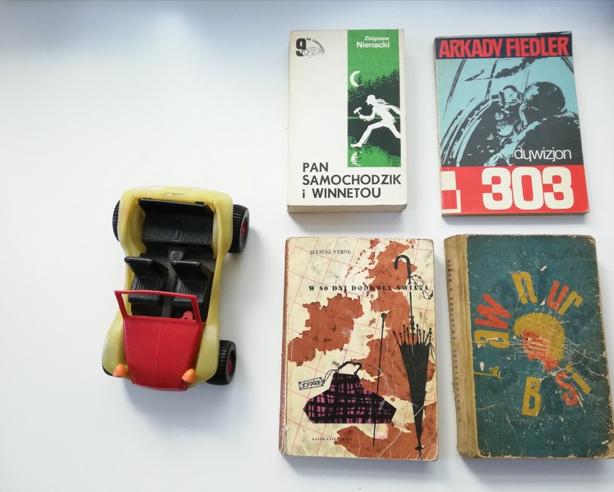 """The photograph features a plastic red-and-yellow toy car. The inside of the car and its tyres are black. Next to the car there are four old slightly tattered books: """"Pan samochodzik i Winnetou"""" (Mister Automobile and Winnetou), """"Dywizjon 303""""(303rd Squadron RAF), """"W 80 dni dookoła świata"""" (Around the World in Eighty Days), """"Awantura o Basię"""" (Argument About Basia)."""