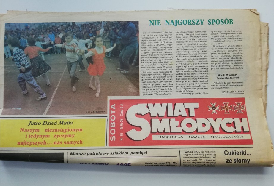 """The photograph presents an old periodical """"Świat Młodych. Harcerska Gazeta Nastolatków"""" (Youth's World. The Scout Periodical for Teenagers) (the white text on the red background). The periodical is white but its rims are yellowed and tattered. The text is black. In the left top corner a colourful picture of dancing children is printed. In the background some spectators can be seen. The texts of the articles are illegible but some headlines can be read: Tomorrow is the Mother's Day. We wish all the best to our irreplaceable and only…, Straw … candies, Not the worst way."""