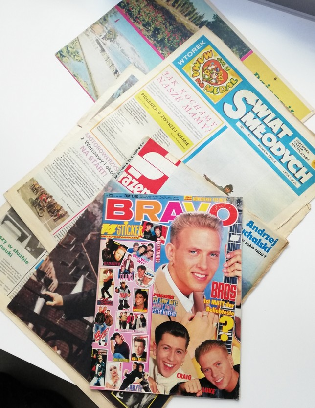 The photograph features some old and slightly tattered newspapers and periodicals: Bravo, Together, Youth's World.