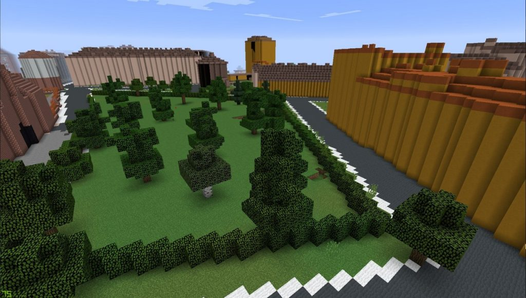 Gdańsk. Embankment Square. Minecraft visualisation. The photograph presents a square made of green blocks and numerous trees. The square is surrounded by streets constructed from grey blocks. There are some buildings around the square.