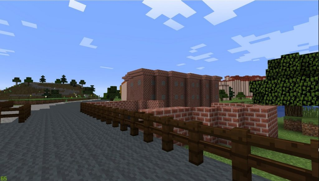 Gdańsk. The auxiliary mill. Minecraft visualisation. The photograph presents an old, low (two-storey), brick building without windows, a brick wall and a bridge over the river. Some old and new tenement houses, trees and a hill visible in the background.