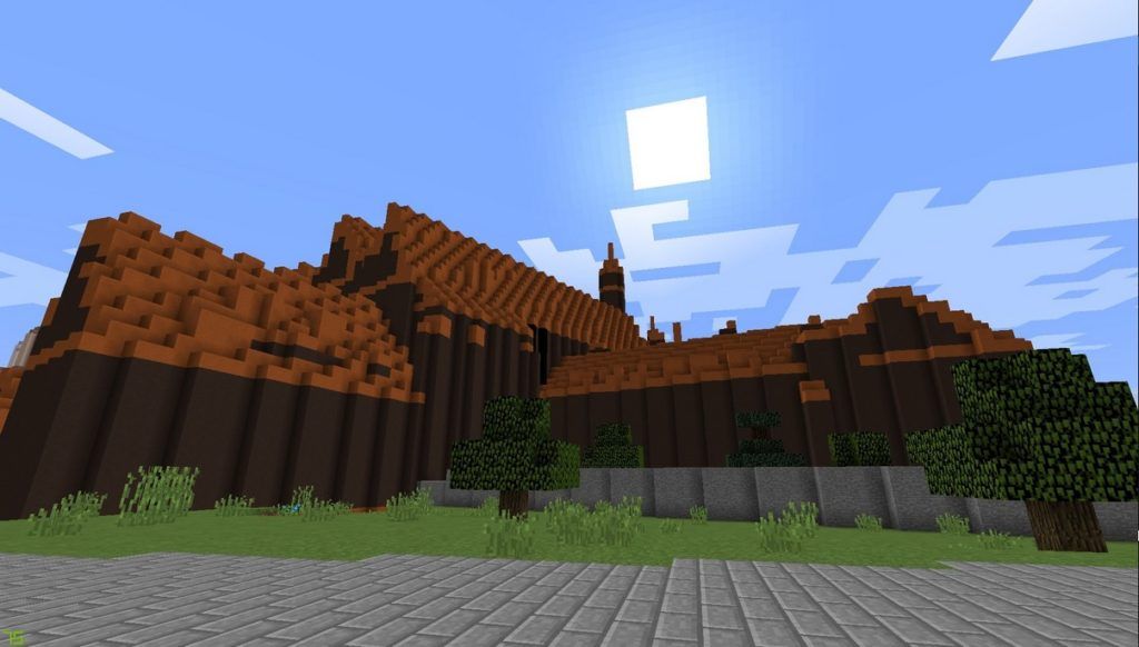 Gdańsk. The National Museum. Minecraft visualisation. The photograph presents a big building constructed from dark brown blocks with the roof constructed from light brown blocks. In front of the building there is a grey cobbled path and some trees.